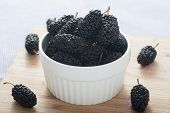 picture of mulberry  - Group of black mulberries in a bowl on the table - JPG