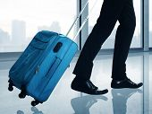 stock photo of carry-on luggage  - Man carrying suitcase walking through the airport hallway - JPG