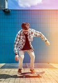 picture of skateboard  - Skateboarder jumping in city on skateboard at the background wall tiles - JPG