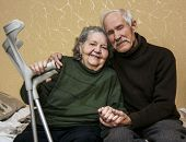 stock photo of crutch  - Grandpa in a dark sweater gently embracing grandmother who keeps him at arm crutches - JPG