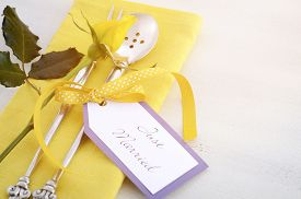 stock photo of yellow buds  - Yellow and white theme wedding table place setting with antique silverware napkin and yellow rose bud on white shabby chic table with applied retro style filters and added lens flare - JPG