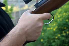 pic of shotgun  - Detail of a mans hand holding shotgun - JPG