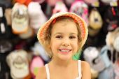 Portrait Of Little Girl Trying Panama In Store And Smiling, Counter With Commodity