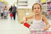 Little Girl Sitting In Store Cart And Looking At Side, Shelves With Commodity