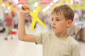 Little Caucasian Boy Holding Yellow Boomerang Toy, Standing In Big Store