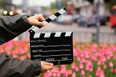 Junta de badajo de cine en las manos del muchacho en campo con tulipanes en calles urbanas