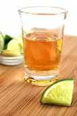 stock photo of mezcal  - Shooter glass with tequila and lime on wood cutboard - JPG