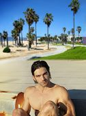 Young shirtless hunky man at beach with blue sky and palm trees