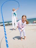 Summer vacation - girl playing with skipping rope on the beach