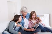 Senior woman with grandkids playing with touchpad