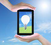 Glühbirne auf Tablet PC in Frauen-hand