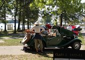 stock photo of mg  - Woman at Car Show with Hat On at Side of Lake by Green Car - JPG