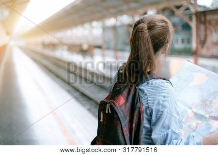 poster of Young Woman Traveler Holding Map While Looking For Some Direction At Train Station For Travel. Trave