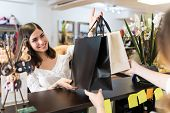 Smiling Beautiful Young Woman Receiving Shopping Bags From Shop Owner At Checkout poster