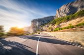 Mountain Road At Sunrise With Motion Blur Effect. Asphalt Road And Blurred Background With Rocks, Bl poster
