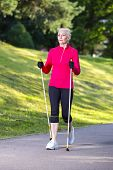 Portrait Of Smiling Sportive Senior Woman Doing Nordic Walking In Park. Vertical Image Composition poster