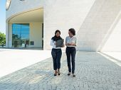 Happy Confident Female Business Partners Discussing Contract Outside. Multiethnic Women In Office Su poster