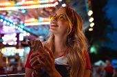 Close up of a cheerful young blonde woman spending fun time at the amusement park, using mobile phon poster