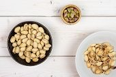 Lot Of Whole Lot Of Pieces Of Ripe Green Pistachio In Tiny Wooden Bowl In Dark Ceramic Bowl In White poster