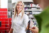 Female Pharmacist With a Male Customer in Pharmacy Drugstore.
