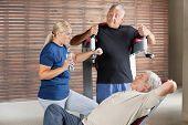 Three senior people talking in gym while having a break