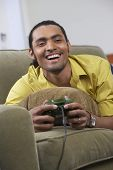 Man laying on couch playing video games