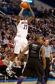 LOS ANGELES - MARCH 12: Arizona Wildcats G Kyle Fogg #21 shoots over Washington Huskies G Isaiah Tho
