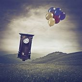 stock photo of pendulum clock  - Pendulum flying over a meadow with some balloons - JPG