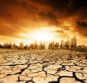 stock photo of global-warming  - A Global Warming Concept Image with cracked earth in front of a polluted city - JPG