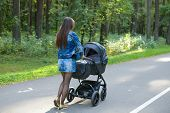 Slender Mother Walks With A Stroller In The Park. Fashionable Young Woman With A Stroller For A Walk poster