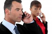young businessman making a call and female colleague in background