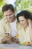 pic of early 60s  - Son Showing Mother How to Use Mp3 Player - JPG