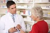picture of dispenser  - American pharmacist with senior woman in pharmacy - JPG