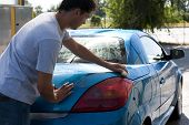 picture of car wash  - Young man washing his car with sponge - JPG