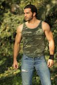 Natural outdoor portrait of masculine muscular handsome male model in came tank top and ripped jeans