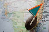 Macro Shot Of A Flag And Football Placed On Miami, Florida In A Map. poster