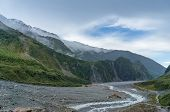 Beautiful Glacier Valley Landscape With Mountain Cliffs Covered In Forest And Waterfalls And Hiking  poster