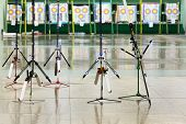 Five big sport bows stand on stilts inside shooting gallery