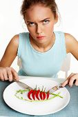 Portrait of frowning girl with fork and knife in hands and plate with red hot chili peppers in front