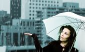 Beautiful young woman with white umbrella on rainy day