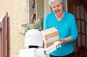 Autonomous Ai Artificial Intelligence Robot Is Delivering Parcels Or Boxes, Senior Woman Is Receivin poster