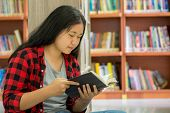 Portrait Of Clever Student With Open Book Reading It In College Library poster