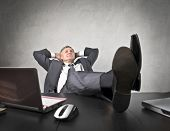 foto of peg-leg  - Senior businessman lying on his office chair with his feet on the desk - JPG