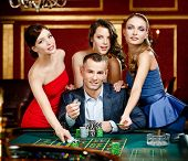 Man surrounded by women plays roulette at the casino club