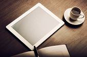 Tablet Pc And A Coffee And Notebook With Pen On The Office Desk