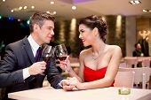 happy affectionate couple at restaurant toasting and looking at each other