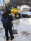 man with a shovel looks like a tractor clears snow from the street