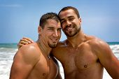 image of gay couple  - Two shirtless gay man standing at the beach - JPG