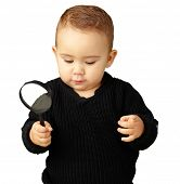 Baby Boy holding a magnifying glass against a white background