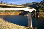 stock photo of stratus  - A concrete arch bridge spans a reservoir at low water level - JPG
